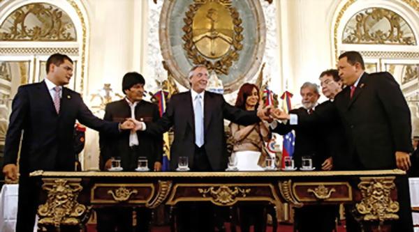 Néstor Kirchner estrecha la mano de Hugo Chávez y le dirige una mirada y sonrisa pícara al presidente de Venezuela, de comportamiento respetuoso protocolar.