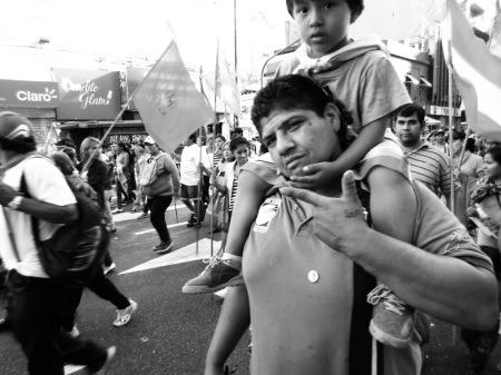 Domingo 24 de marzo pasado: un militante de sectores populares, con su hijito en hombros, marcha en columna a Plaza de Mayo para la concentración central en recuerdo de los 30 mil asesinados por la última dictadura militar argentina, iniciada en 1976. Foto por Amílcar Moretti.