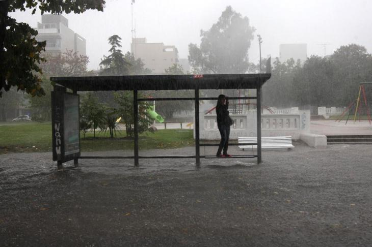 Vecina espera el micro urbano subida a un caño del parador. La plaza central de la ciudad, inundada. De La Nación.com